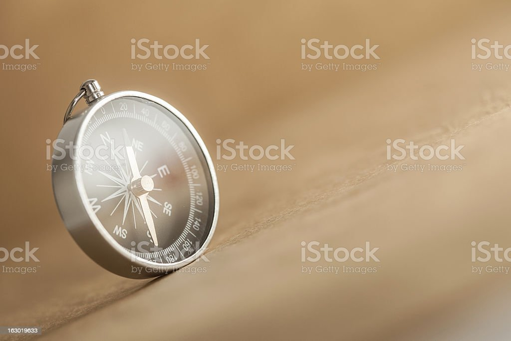 Compass on Light Brown Background royalty-free stock photo