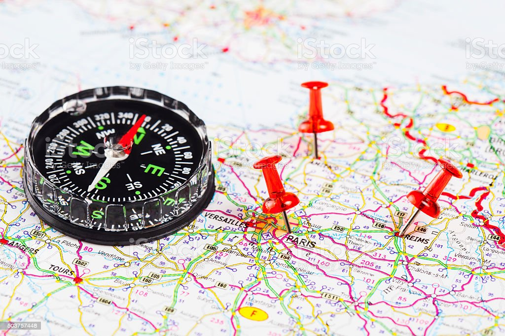 Compass on map with push pins stock photo