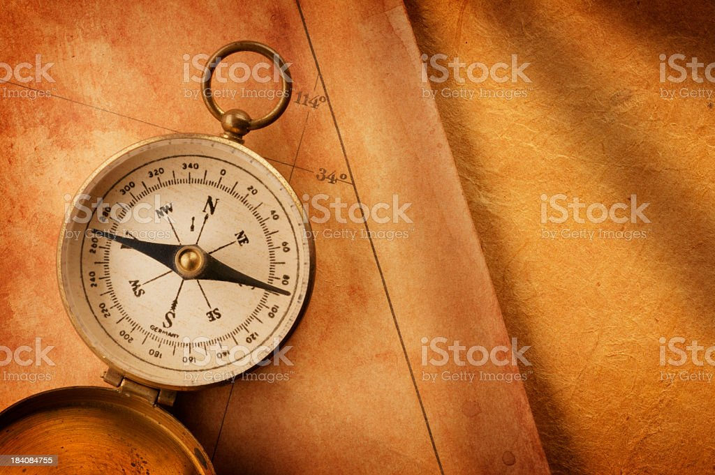 Compass on Old Antique Map With Strong Directional Lighting royalty-free stock photo