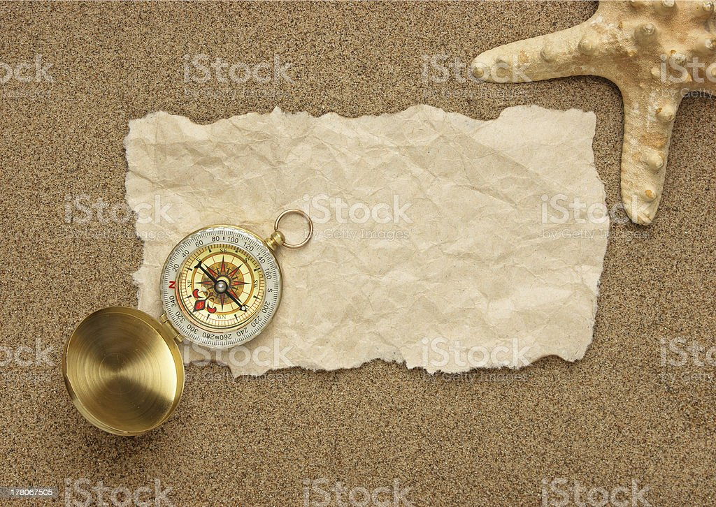 Compass on old sheet paper against the background of sand royalty-free stock photo