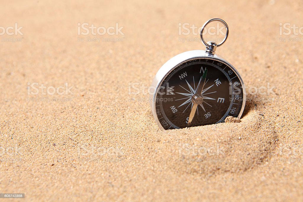 Compass on the sea sand stock photo