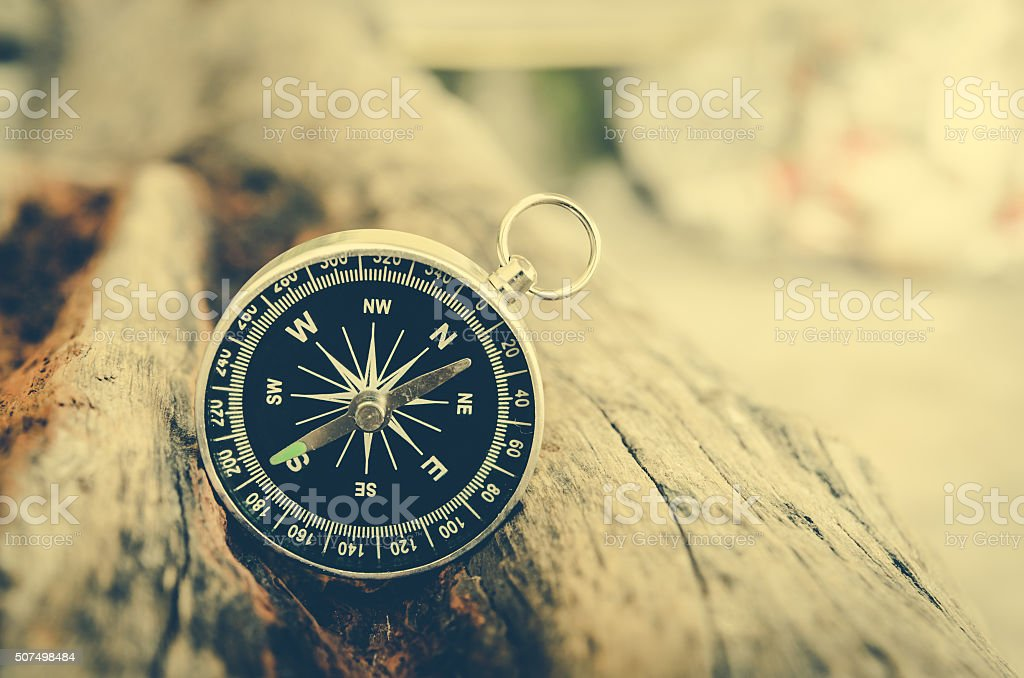compass on wood log . process in vintage color tone stock photo