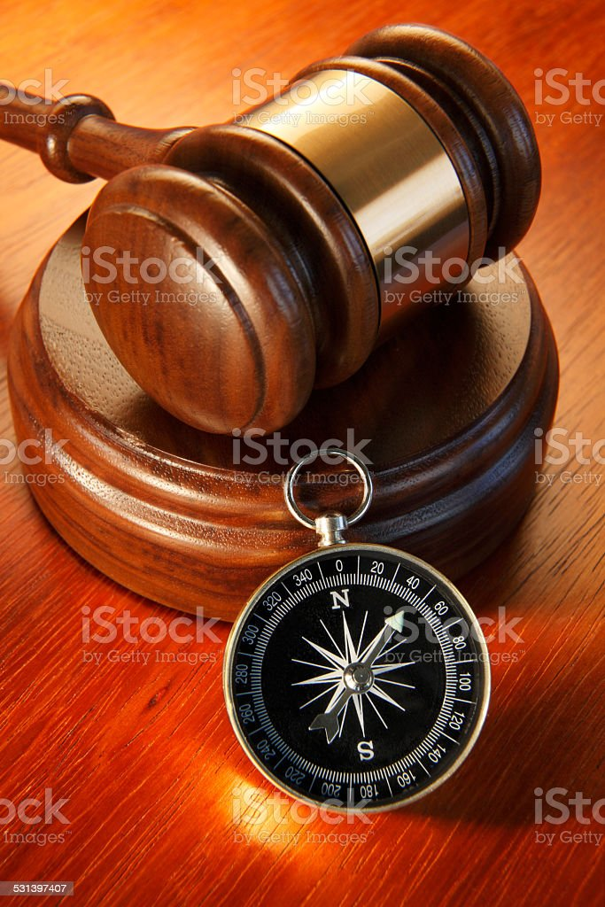 Compass sitting at base of a gavel and sound block stock photo