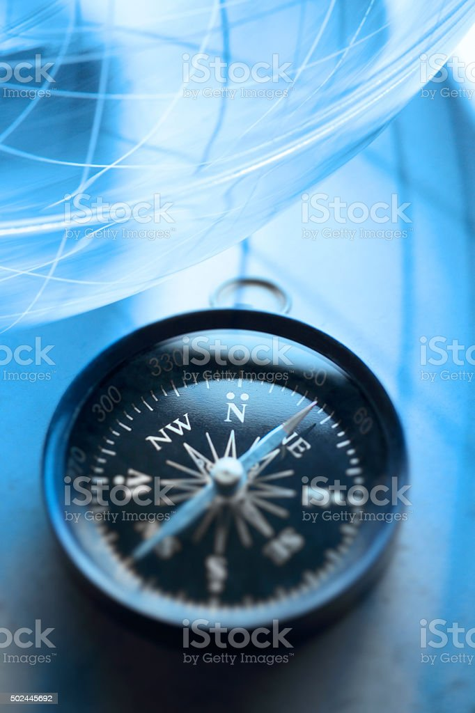 Compass Sitting Below A Globe stock photo