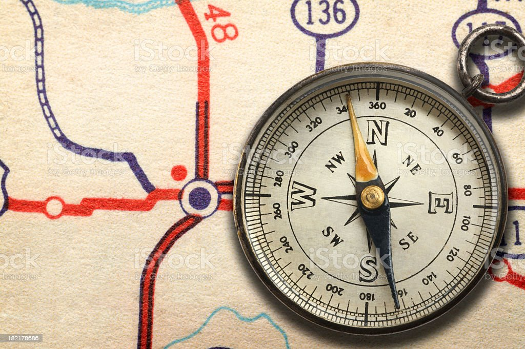 Compass sitting on top of road map showing highway junction stock photo