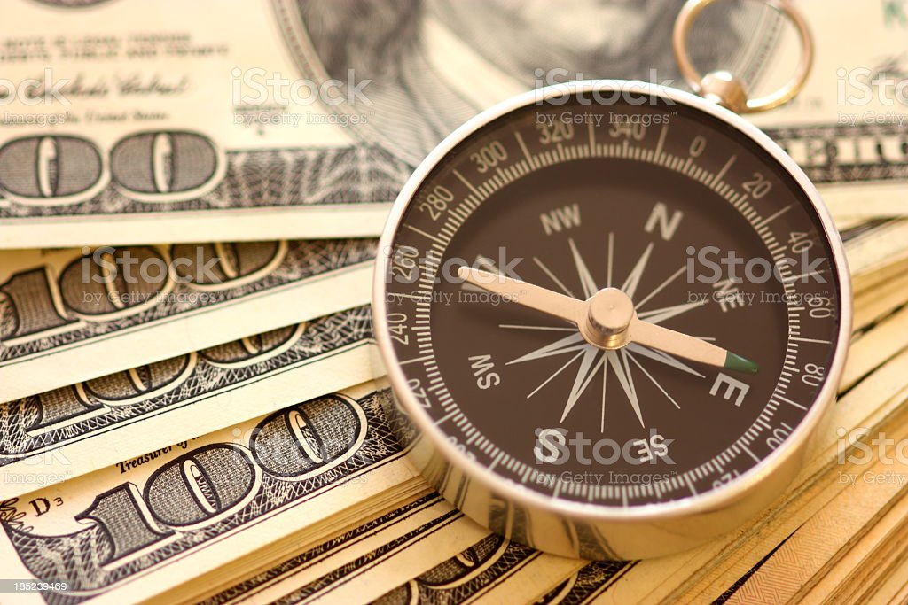 Compass used as paperweight on top of 100 dollar bills stock photo