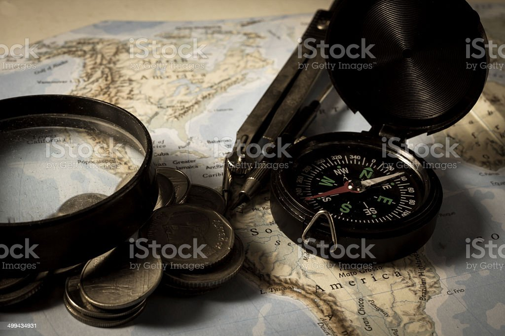 Compass with magnifier and ccoins on map royalty-free stock photo