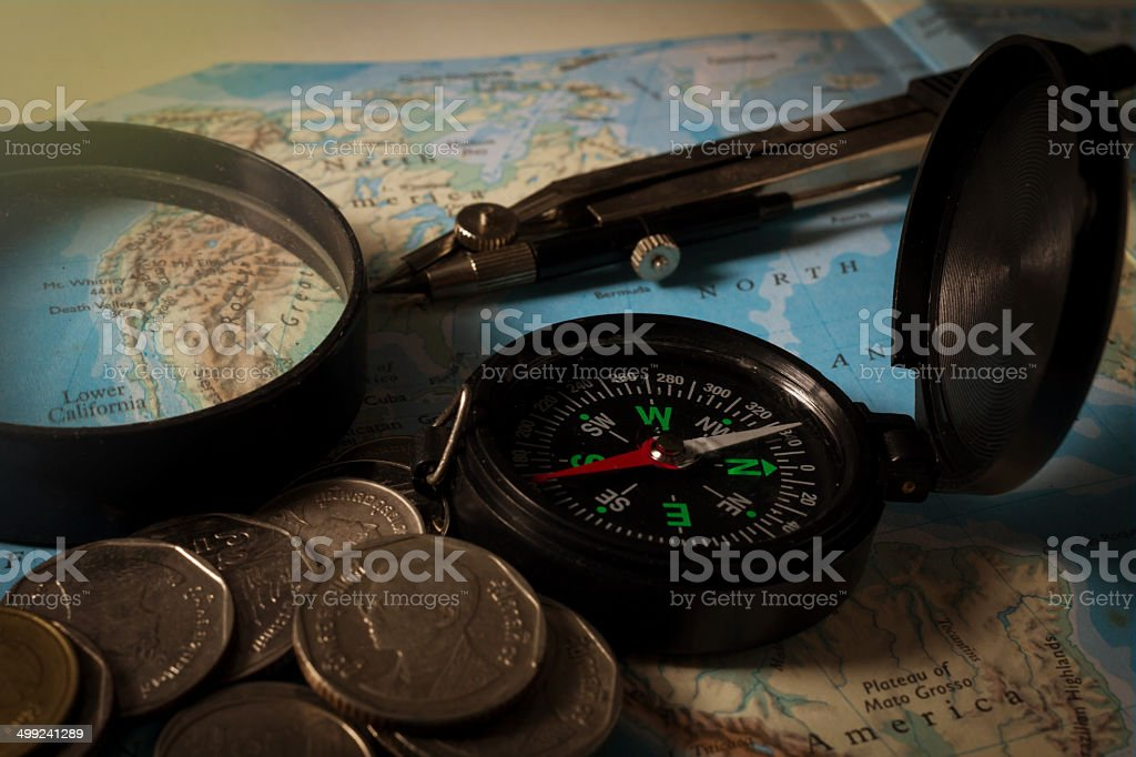 Compass with magnifier and coins on map royalty-free stock photo