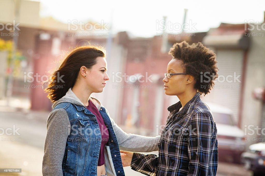 Compassionate young woman reaches out to console her friend stock photo