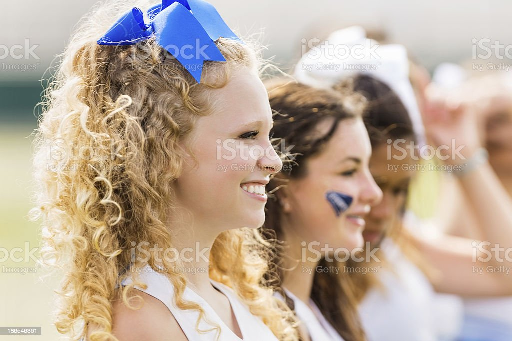 Competitive cheerleading squad cheering at football game royalty-free stock photo