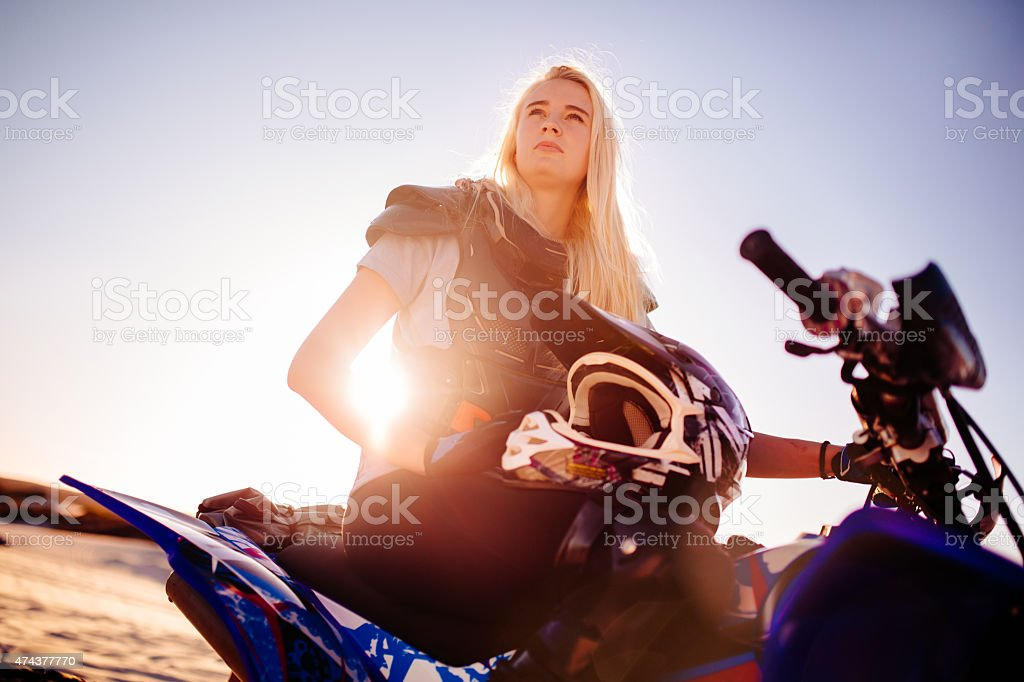 Competitive female quad bike racer looking intent with sun flare royalty-free stock photo