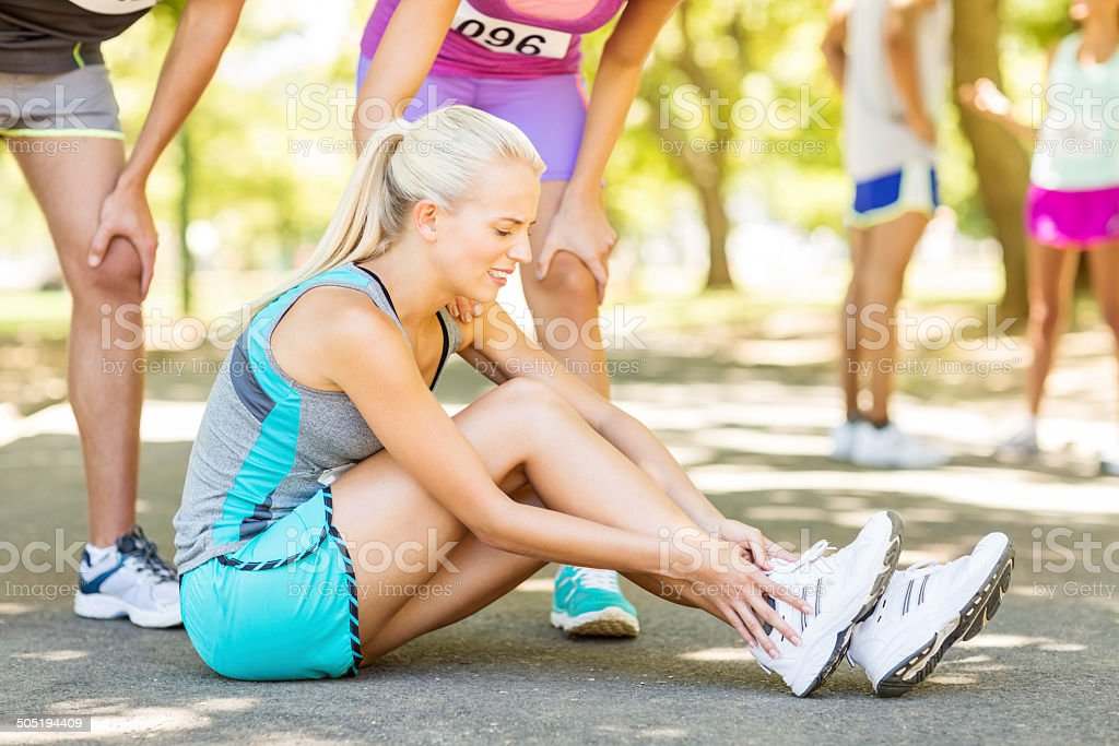 Competitors Consoling Marathon Runner Suffering From Ankle Injury stock photo