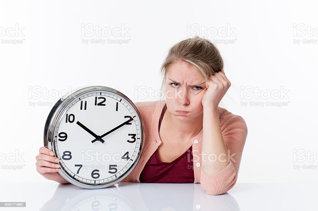 complaining beautiful young blond woman holding a clock stock photo
