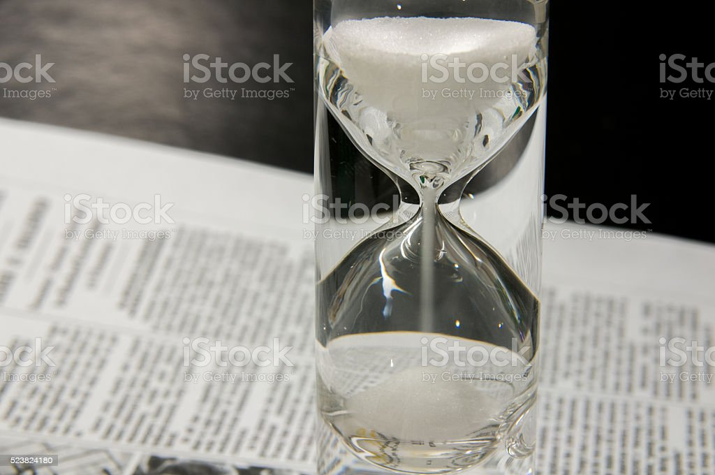 Completely filled sandglass on newspaper stock photo