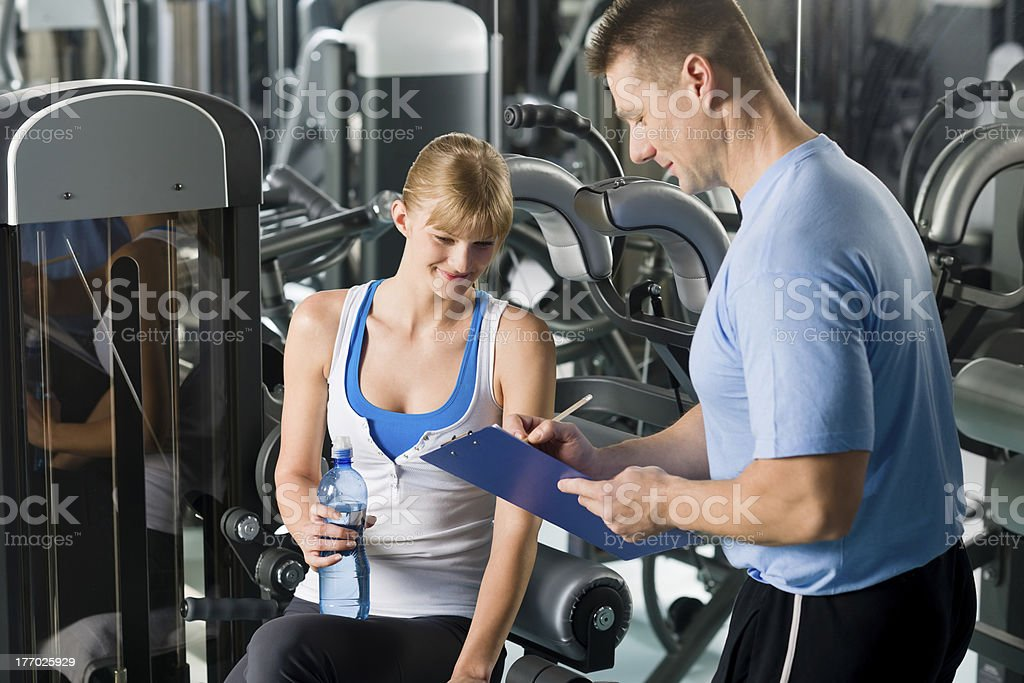 Completing personal fitness plan with trainer royalty-free stock photo