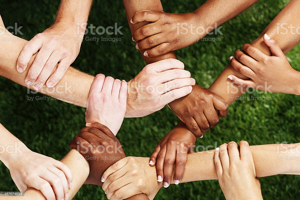 Complex linking of many mixed hands: unity is strength! stock photo