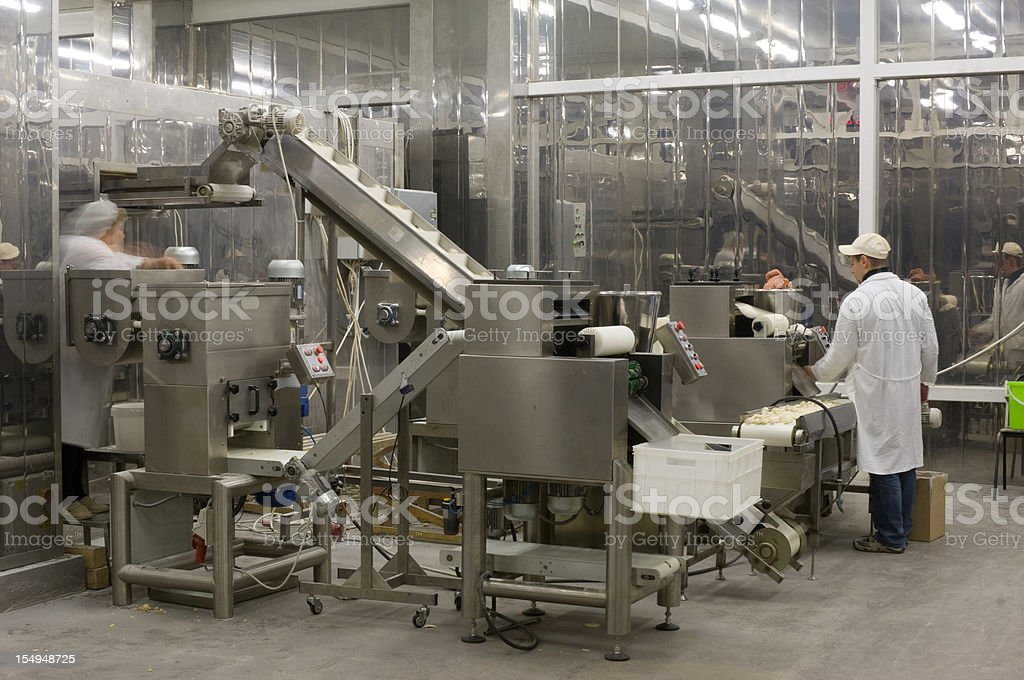 A complex production line with workers in a food factory stock photo