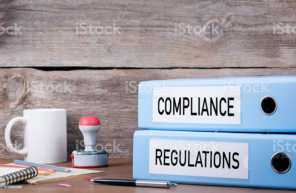 Compliance and Regulations. Two binders on desk stock photo
