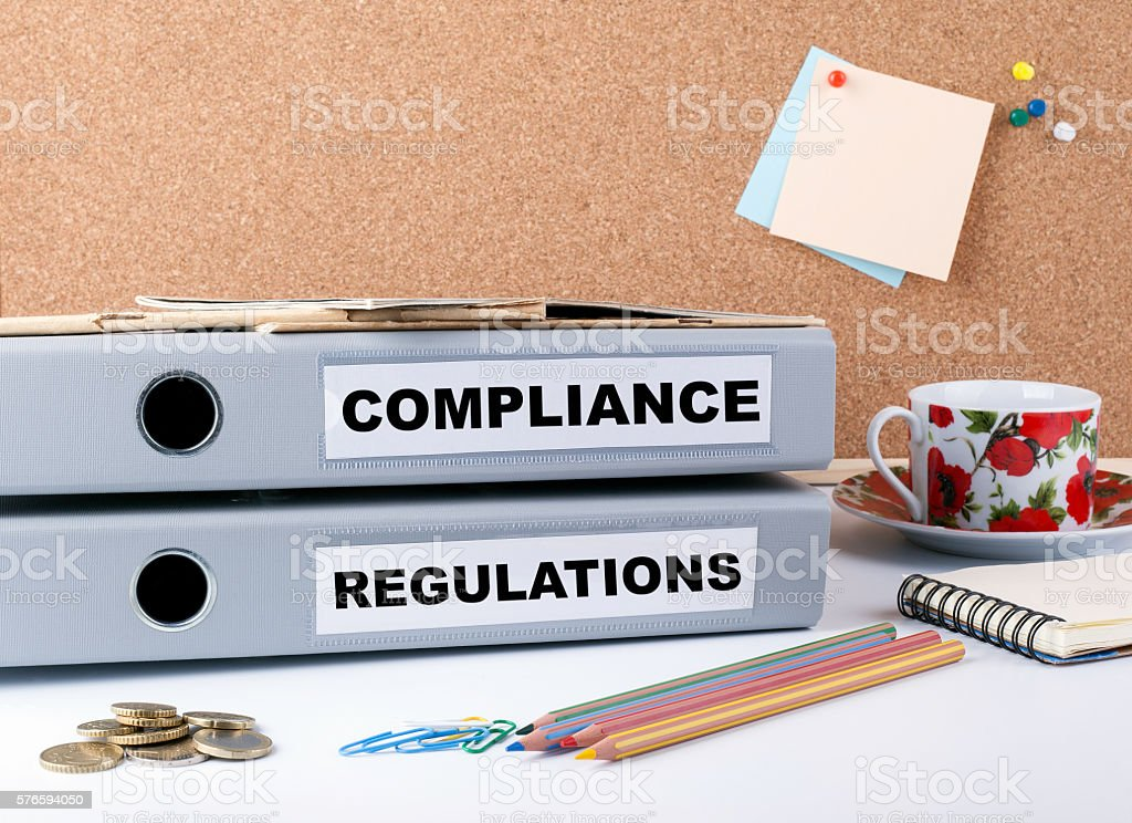 Compliance and Regulations - two folders on white office desk. stock photo