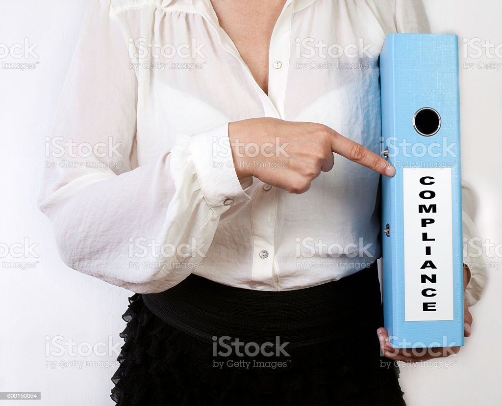 Compliance. Business women holding binder stock photo
