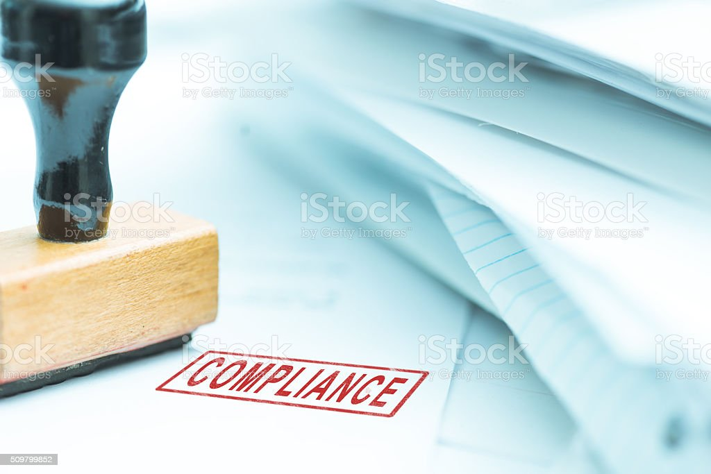 Compliance stamp on papers stock photo