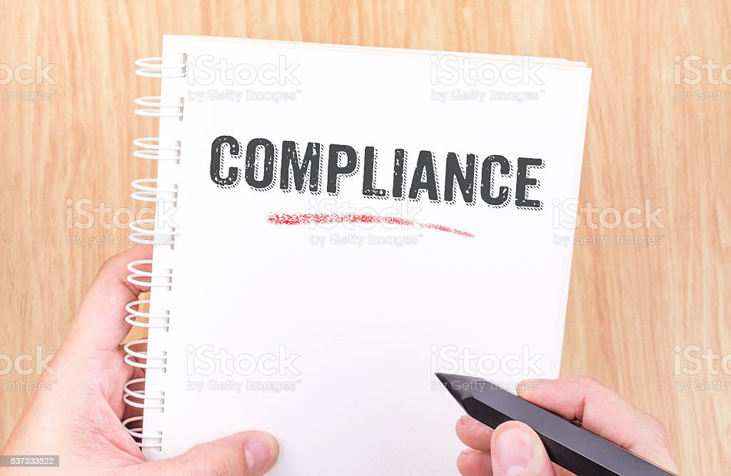 Compliance word on white ring binder notebook with hand holding stock photo