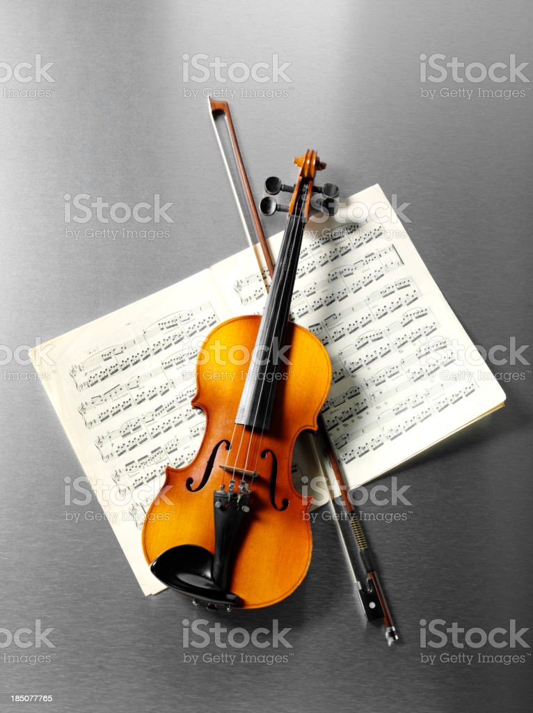 \'Overhead view of a wooden violin and bow on sheet music,with a...