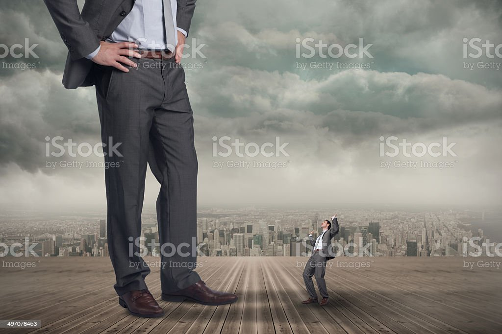 Composite image of businessman posing with hands up and giant stock photo