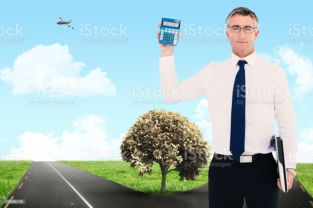 Composite image of businessman showing calculator while holding his laptop stock photo