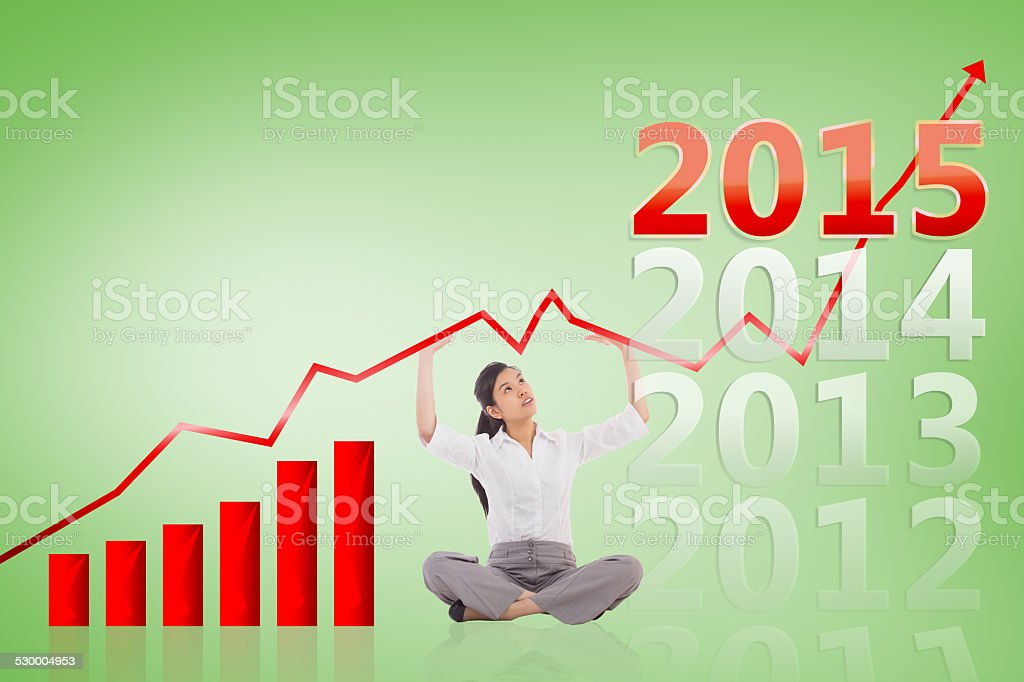 Composite image of businesswoman sitting cross legged pushing up stock photo
