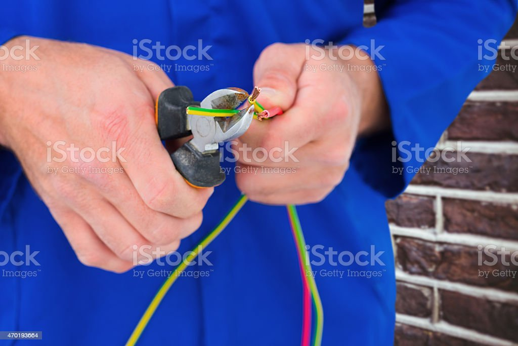Composite image of electrician cutting wire with pliers stock photo
