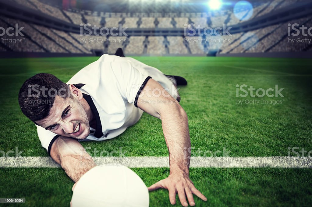 Composite image of man lying down while holding ball stock photo