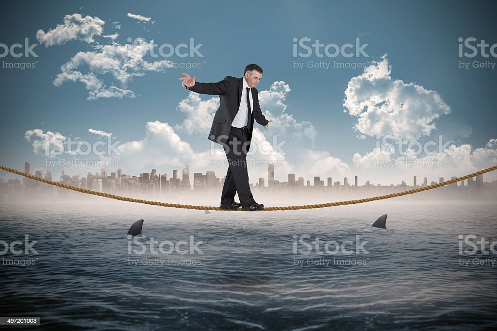 Composite image of mature businessman doing a balancing act stock photo