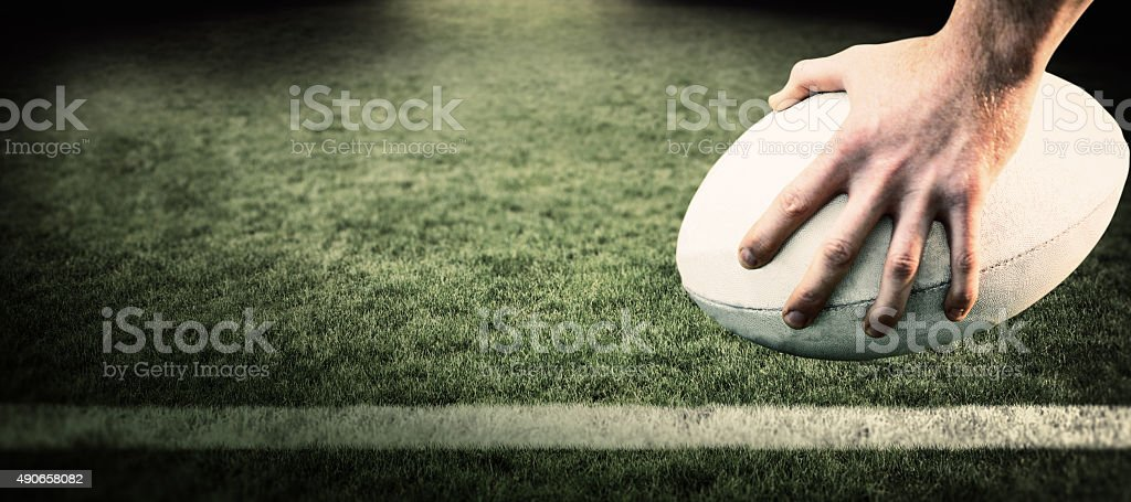 Composite image of rugby player posing feet on the ball stock photo
