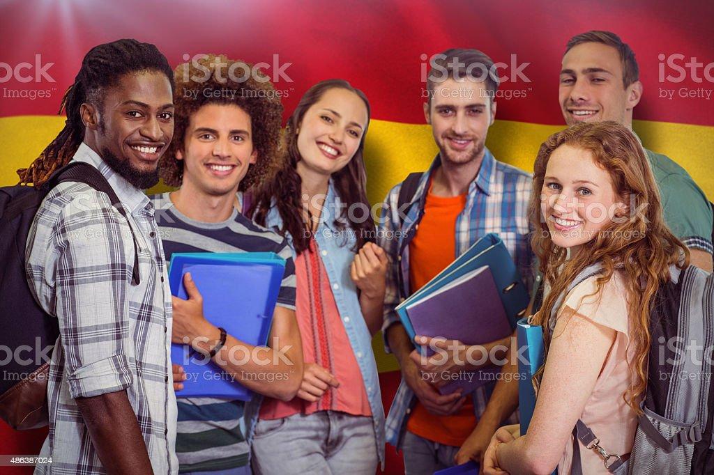 Composite image of smiling students holding folder stock photo