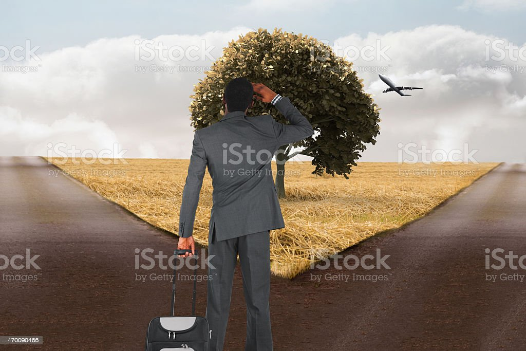 Composite image of young businessman standing with suitcase stock photo