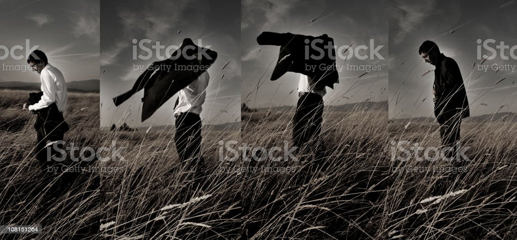 Composite of Man Getting Dressed in Field with Overcast Sky stock photo