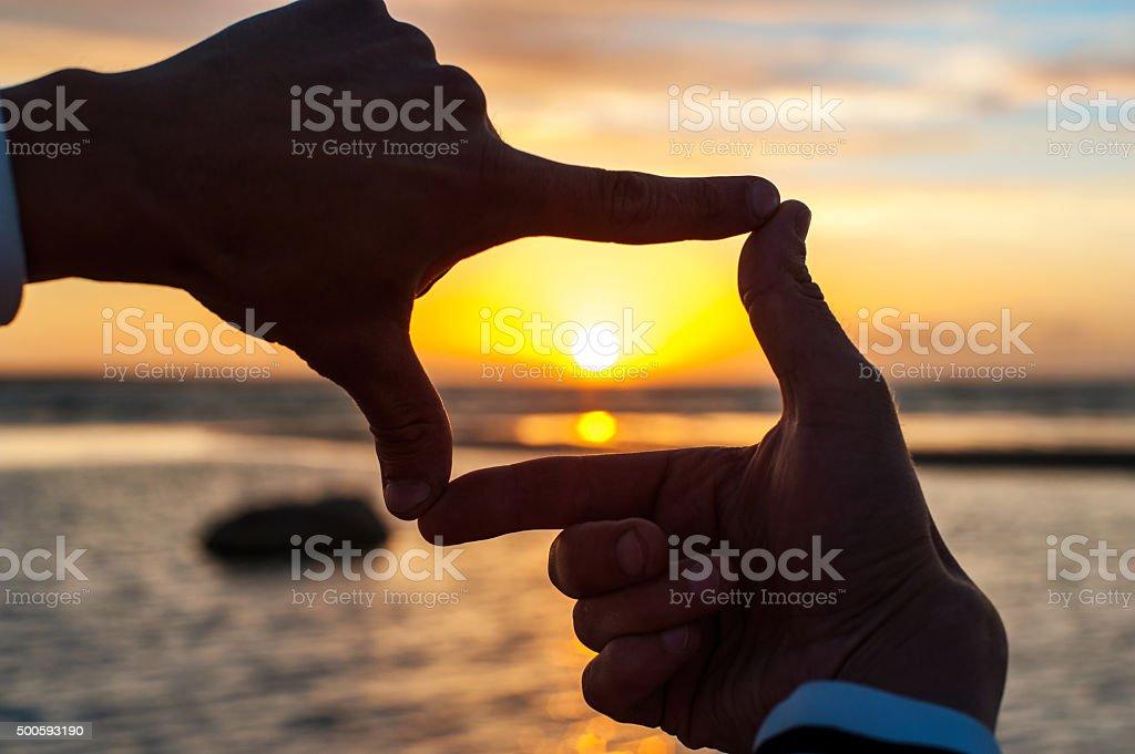 Composition finger frame- man's hands capture the sunset stock photo