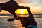 Composition finger frame- man's hands capture the sunset