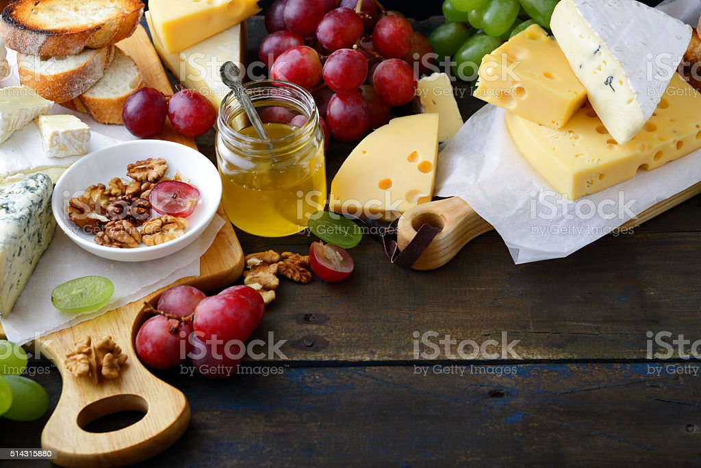 Composition of different types cheeses, grapes, honey, bread and walnuts stock photo