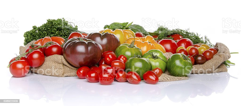 Composition of different varieties of tomatoes and herbs stock photo
