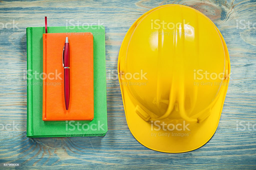 Composition of hard hat notepads pen on wooden board constructio stock photo