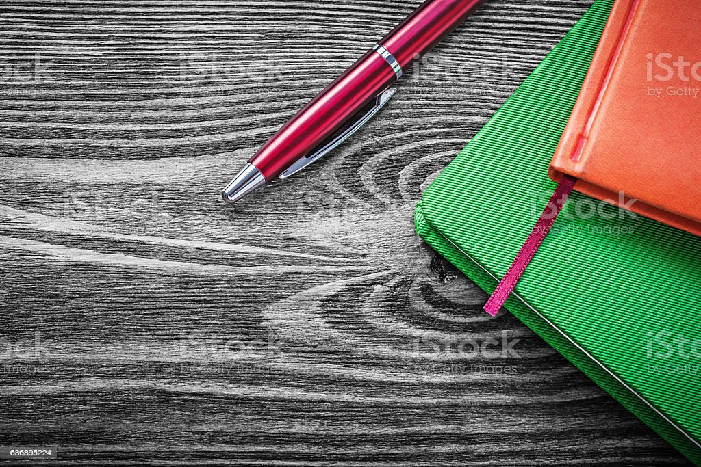 Composition of notepads ballpoint pen on vintage wooden board stock photo