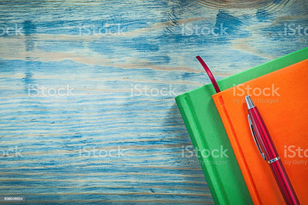 Composition of notepads pen on wooden board office concept stock photo