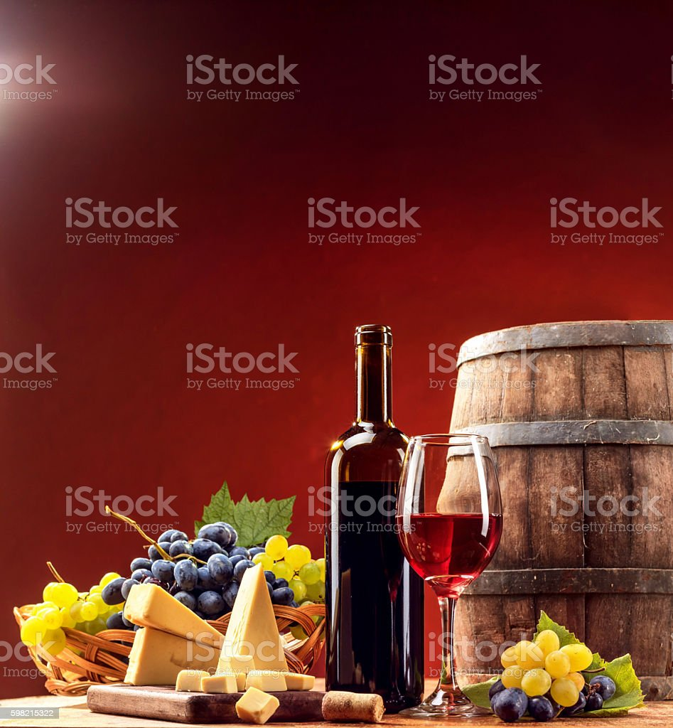 Composition of red wine glass and bottle with food stock photo