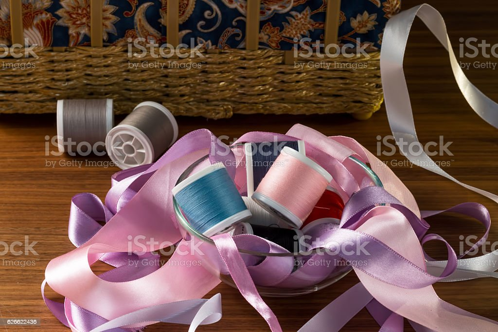Composition of ribbons and thread on a wooden table. stock photo