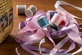 Composition of ribbons and thread on a wooden table.