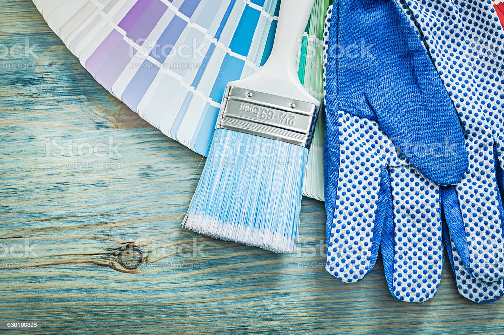 Composition of safety gloves color sampler paint brushes on wood stock photo