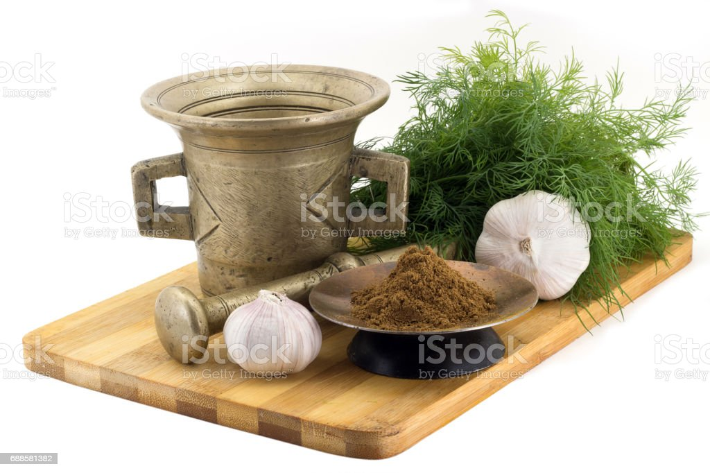 Composition of spices, Indian masala, dill, garlic, vintage spice grinder isolated on white background stock photo