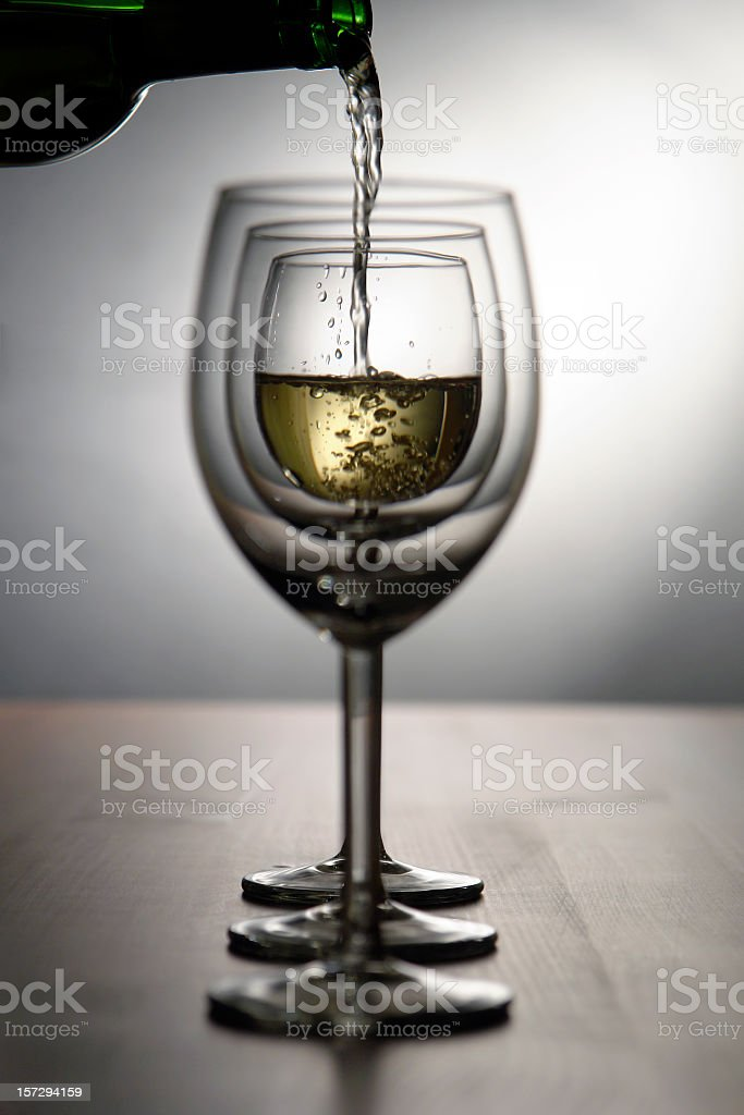 Composition of three white wine glasses, pouring wine, studio shot royalty-free stock photo